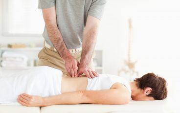 Brunette woman getting a back-massage in a room
